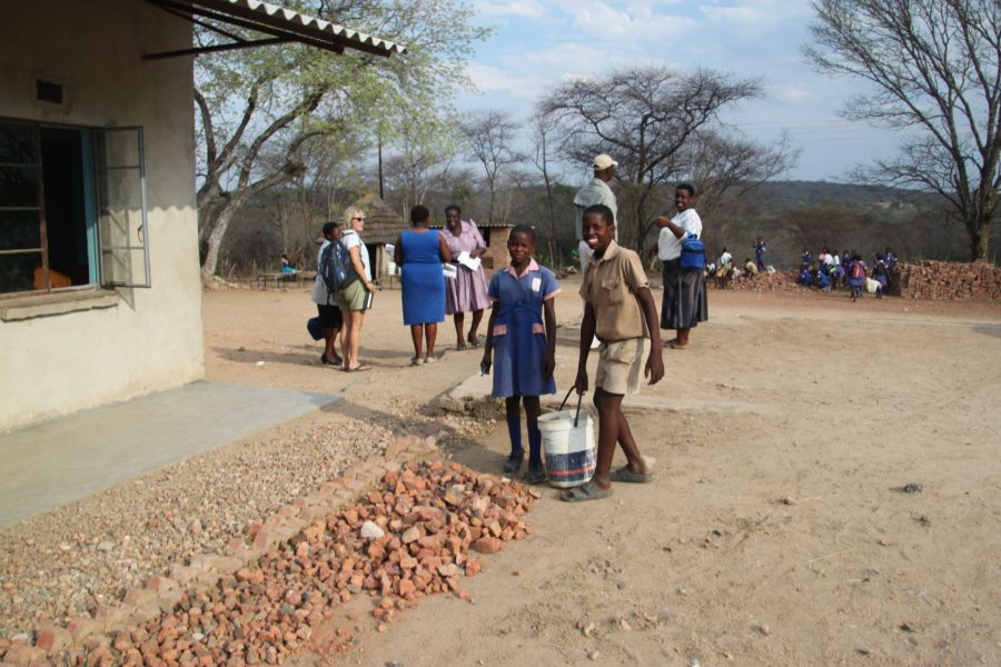 After breaking up the bricks, the kids haul them over and spread them as landscaping in their schoolyard